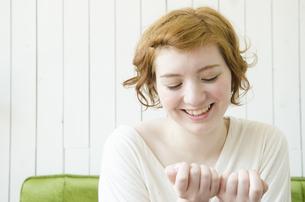 室内で自分の爪を見ているハーフの女性の素材 [FYI01077440]