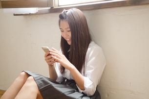 床に座って携帯電話を見ている制服姿の女性の素材 [FYI01077475]