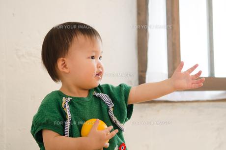 オレンジを持って手を伸ばしている女の子の素材 [FYI01077525]
