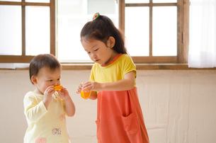 オレンジを食べている姉妹の素材 [FYI01077548]