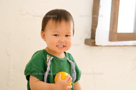 オレンジを持って笑っている女の子の素材 [FYI01077591]