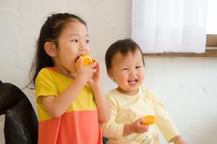 オレンジを食べている姉妹の素材 [FYI01077607]