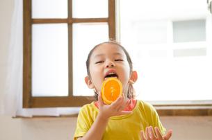 オレンジを食べている女の子の素材 [FYI01077612]