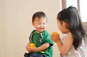 オレンジを持って笑っている姉妹の素材 [FYI01077639]