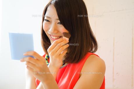 鏡を見ながらメイクを直している女性の素材 [FYI01077776]