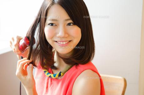 ヘアアイロンで髪の毛をセットしている女性の素材 [FYI01077777]