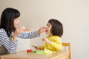 果物を食べている姉妹の素材 [FYI01077964]