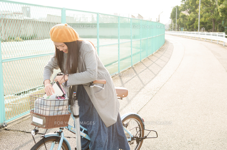 自転車の荷物を触っている女性の素材 [FYI01078007]