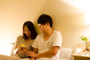 ベッドで目覚まし時計をセットするカップルの素材 [FYI01078103]