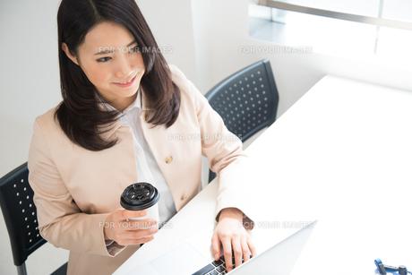 コーヒーを片手にパソコンを触っている女性の素材 [FYI01078456]