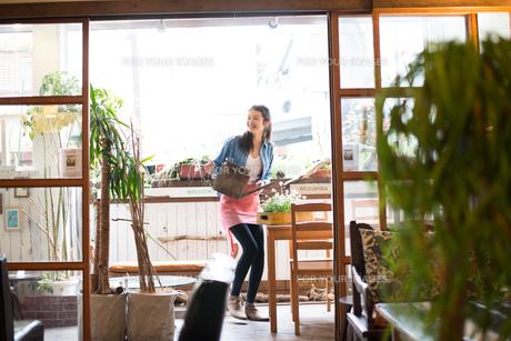 ジョーロを持って笑っている女性の素材 [FYI01078657]