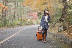 秋の紅葉した公園でトランクを引いている女性の素材 [FYI01096551]