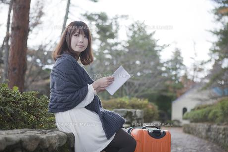 秋の石畳にトランクを置いて本を読む女性の素材 [FYI01096740]