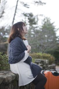 秋の石畳にトランクを置いて本を読む笑顔の女性の素材 [FYI01096794]