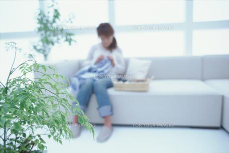 ソファで針仕事をする女性のシルエットの素材 [FYI01121267]