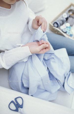ソファに座って裁縫をする女性の素材 [FYI01122477]