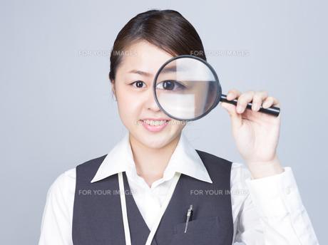大きな虫眼鏡で目を拡大する女性の写真素材 [FYI01166308]