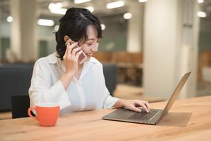 オフィスでPCを広げながら通話中のOL女性の写真素材 [FYI01216303]