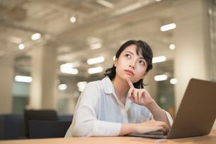 会社のデスクでPCを開いて考えこむOL女性の写真素材 [FYI01216306]