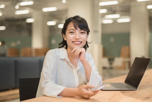会社のデスクで談笑中のOL女性の写真素材 [FYI01216307]