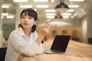 会社のデスクで携帯を持っているOL女性の写真素材 [FYI01216308]