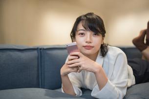 ソファに寝転がり笑顔携帯を持つOL女性の写真素材 [FYI01216311]