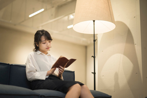 ソファに座り本を読むOL女性の写真素材 [FYI01216316]