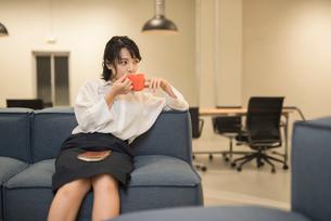 休憩中にソファに座り飲み物を飲むOL女性の写真素材 [FYI01216318]