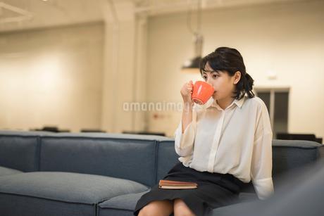休憩中にソファに座り飲み物を飲むOL女性の写真素材 [FYI01216320]