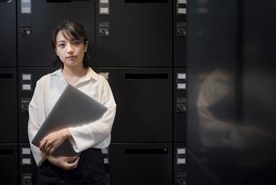 ロッカールームでPCを抱える女性の写真素材 [FYI01216330]
