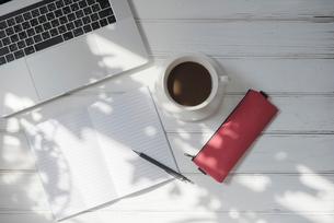 木漏れ日とPCとコーヒーカップとノートとペンの写真素材 [FYI01216603]