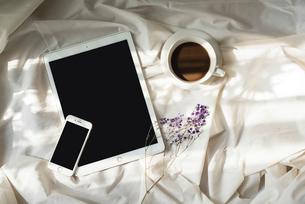 光が差し込む、iPadとiPhoneとコーヒーカップと花の写真素材 [FYI01216618]