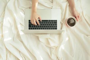 白い布の上にPCを置き片手で操作しながら、もう片方の手でカップを持つの写真素材 [FYI01216636]