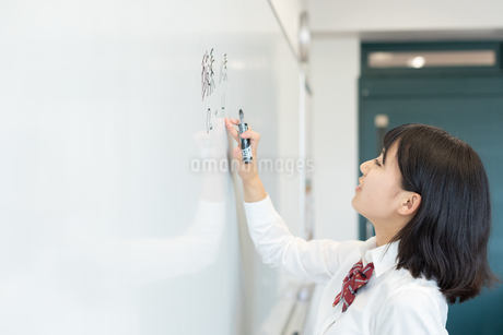 教室のホワイトボードに文字を書く女子高校生の写真素材 [FYI01220764]