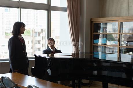 ピアノの前で会話する女子高校生の写真素材 [FYI01220775]