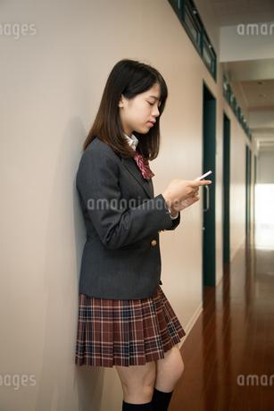 スマートフォンを操作する女子高校生の写真素材 [FYI01220855]
