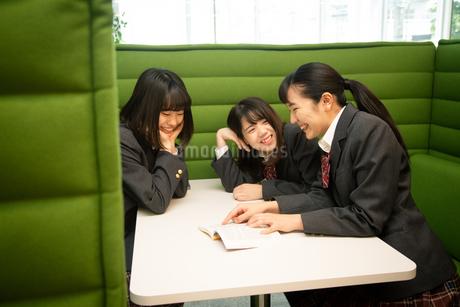 テーブルで本を見る3人の女子高校生の写真素材 [FYI01220869]