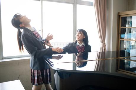 音楽室のピアノの前にいる女子高校生の写真素材 [FYI01220890]