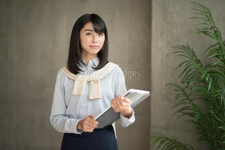 iPadを持って微笑む20代OL女性の写真素材 [FYI01224954]