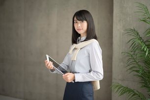 iPadを抱えて立つ20代OL女性の写真素材 [FYI01224961]