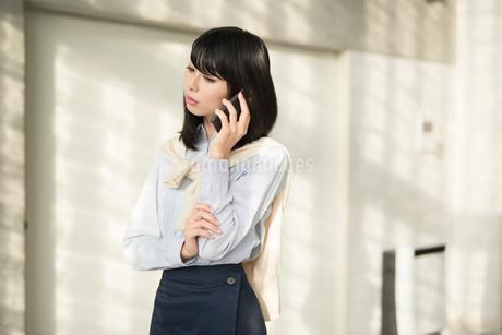 iPhoneで通話しながら考え込む20代OL女性。目線外し。の写真素材 [FYI01225174]