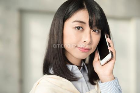 iPhoneで通話中の20代OL女性。顔寄り。の写真素材 [FYI01225180]