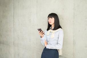 壁に寄りかかりiPhoneを片手で持ち画面を見ながら、呆れたように前を見ている20代OL女性。の写真素材 [FYI01226692]