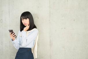 iPhoneを持ち、頬に手を当ててこちらを見る20代OL女性の写真素材 [FYI01226695]