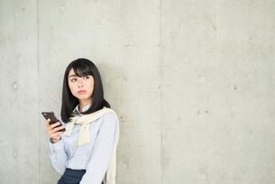 iPhoneを持ちながら目線を右に向けている20代OL女性の写真素材 [FYI01226696]