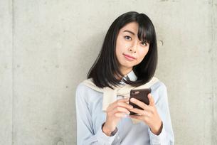 iPhoneを持ちながら微笑む20代OL女性。目線あり。の写真素材 [FYI01226697]