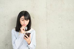 iPhoneの画面を見ながらあごに手を当て考えるOL女性。の写真素材 [FYI01226698]