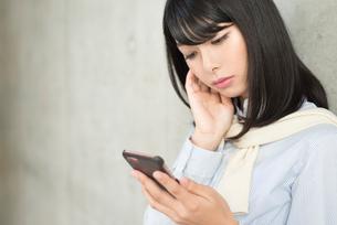 iPhoneを持ちながら考えるOL女性。目線なし。顔の寄り。の写真素材 [FYI01226699]