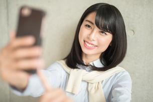 iPhoneを操作している女性(顔にピント)の写真素材 [FYI01226703]