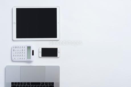 PCのキーボードとiPhoneと計算機とiPad。俯瞰構図。の写真素材 [FYI01226714]